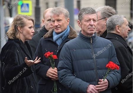 Stock Photo of Anatoly Sobchak's daughter, Russian TV host Ksenia Sobchak, President, Chairman of the Board of Sberbank Herman Gref and Deputy Chief of Staff of the Presidential Administration of Russia Dmitry Kozak (center) are seen before the flower-laying ceremony at the Monument to the First Mayor of Saint Petersburg, Anatoly Sobchak.