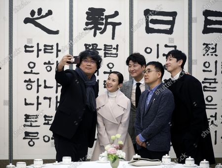 Oscar award-winning film Parasite director Bong Joon-ho takes a photo with cast members Song Kang-ho, Cho Yeo-jeong and Lee Sun-kyun at the Presidential Blue House in Seoul, South Korea, 20 February 2020.