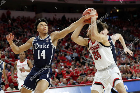 Duke guard Jordan Goldwire (14) reaches in on North Carolina State guard Devon Daniels (24) during the first half of an NCAA college basketball game in Raleigh, N.C