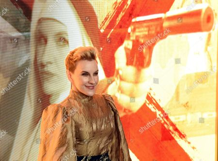 """Kate Mulvany, a cast member in the Amazon Prime Video series """"Hunters,"""" poses against a video image of her character at the premiere of the show at the Directors Guild of America, in Los Angeles"""