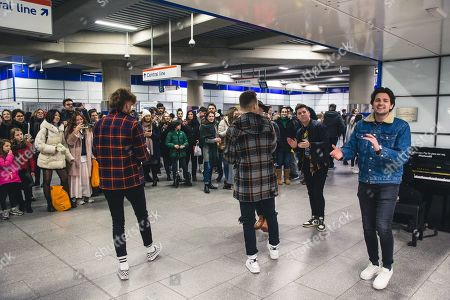 Chris Deaton, Simon Dumas, Chad Michael Jervis, Jordan Harvey, Austin Luther, and Caleb Miller of Nashville 6-peice band, King Calaway, perform an impromptu acoustic show at Tottenham Court Road tube station
