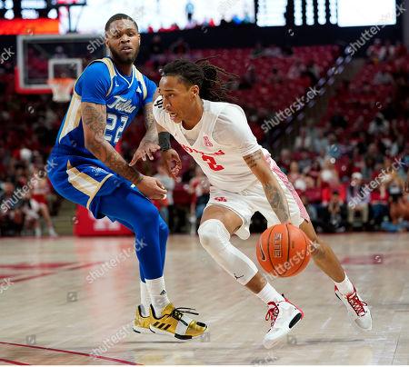 Reggie Jones, Caleb Mills. Houston's Caleb Mills (2) drives toward the basket as Tulsa's Reggie Jones (22) defends during the first half of an NCAA college basketball game, in Houston