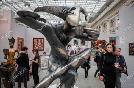 Visitors walk past the sculpture 'Black Coffee' by Russian artist Arsen during the Art Russia contemporary art fair at the Gostiny Dvor in Moscow, Russia 20 February 2020. The exhibition runs from 20 to 23 February 2020.