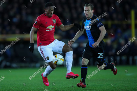 Manchester United's Anthony Martial, left, vies for the ball with Brugge's Ruud Vormer during an Europa League round of 32 first leg soccer match between Brugge and Manchester United at the Jan Breydel stadium in Bruges, Belgium, . Martial scored once and the match ended in a 1-1 draw