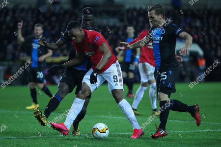 Manchester United's Anthony Martial, center, vies for the ball with Brugge's Odilon Kossounou, left, and Ruud Vormer during an Europa League round of 32 first leg soccer match between Brugge and Manchester United at the Jan Breydel stadium in Bruges, Belgium, . Martial scored once and the match ended in a 1-1 draw