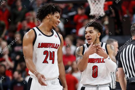 Louisville guard Lamarr Kimble (0) talks to forward Dwayne Sutton (24) during the second half of an NCAA college basketball game against Syracuse, in Louisville, Ky. Louisville won 90-66