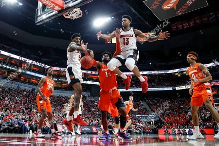 Louisville forward Malik Williams (5) and guard David Johnson (13) battle for a rebound with Syracuse forward Quincy Guerrier (1) during an NCAA college basketball game, in Louisville, Ky. Louisville won 90-66