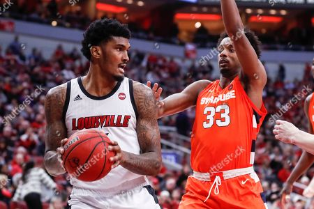 Louisville forward Malik Williams (5) looks to pass as he's defended by Syracuse forward Elijah Hughes (33) during the second half of an NCAA college basketball game, in Louisville, Ky. Louisville won 90-66