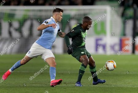 Stock Image of Malmo's Arnor Ingvi Traustason, left, and Wolfsburg's Jerome Roussillon, right, challenge for the ball during the Europa League round of 32 first leg soccer match between VfL Wolfsburg and Malmo FF in Wolfsburg, Germany
