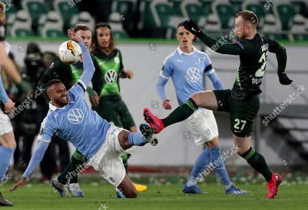 Malmo's Isaac Kiese Thelin, left, and Wolfsburg's Maximilian Arnold, right, challenge for the ball during the Europa League round of 32 first leg soccer match between VfL Wolfsburg and Malmo FF in Wolfsburg, Germany