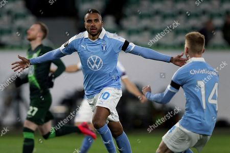 Malmo's Isaac Kiese Thelin, center, celebrates after scoring the opening goal by penalty during the Europa League round of 32 first leg soccer match between VfL Wolfsburg and Malmo FF in Wolfsburg, Germany