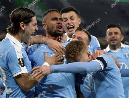 Malmo's Isaac Kiese Thelin, second left, celebrates after scoring the opening goal by penalty during the Europa League round of 32 first leg soccer match between VfL Wolfsburg and Malmo FF in Wolfsburg, Germany