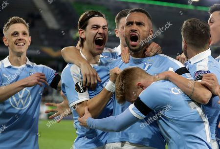 Malmo's Isaac Kiese Thelin, fourth left, celebrates after scoring the opening goal by penalty during the Europa League round of 32 first leg soccer match between VfL Wolfsburg and Malmo FF in Wolfsburg, Germany