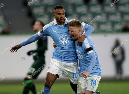 Malmo's scorer Isaac Kiese Thelin, left and his teammate Anders Christiansen, right, celebrate the opening goal scored by penalty during the Europa League round of 32 first leg soccer match between VfL Wolfsburg and Malmo FF in Wolfsburg, Germany