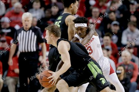 Michigan State's Jack Hoiberg (10) drives around Nebraska's Cam Mack (3) during the first half of an NCAA college basketball game in Lincoln, Neb