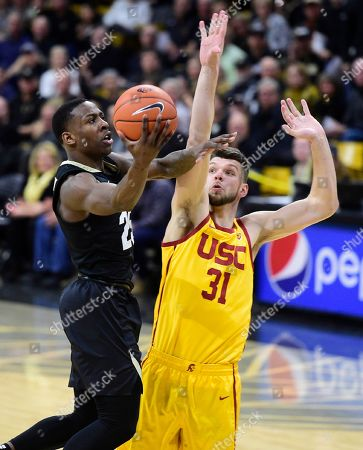 Colorado's McKinley Wright IV drives past Southern California's Nick Rakocevic during the second half of an NCAA college basketball game, in Boulder, Colo