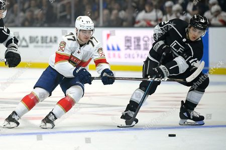 Los Angeles Kings center Trevor Moore, right, takes the puck as Florida Panthers center Frank Vatrano reaches in during the first period of an NHL hockey game, in Los Angeles