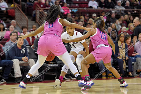 Zia Cooke, Awa Trasi, Jaelyn Richard-Harris. South Carolina's Zia Cooke, back, dribbles while defended by LSU's Awa Trasi (0) and Jaelyn Richard-Harris during the first half of an NCAA college basketball game, in Columbia, S.C. South Carolina won 63-48