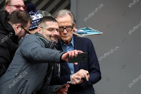 Bill Nighy poses for photographs with a fan as he arrives for the 'Minamata' photocall during the 70th annual Berlin International Film Festival (Berlinale), in Berlin, Germany, 21 February 2020. The movie is presented in the Berlinale Special section at the Berlinale that runs from 20 February to 01 March 2020.