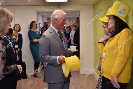 Prince Charles is presented with a Marie Curie yellow hat by community fundraiser Hannah Leckie and Hilary James during a visit to the Marie Curie Hospice in Cardiff.