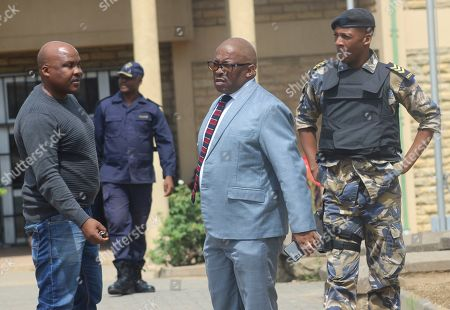 Investigating officer and Lesotho's Deputy Commissioner of Police Paseka Mokete, center, stands with security outside the court in Maseru, Lesotho, . Lesotho's Prime Minister Thomas Thabane failed to show up in court to be charged with murder in the killing of his estranged wife