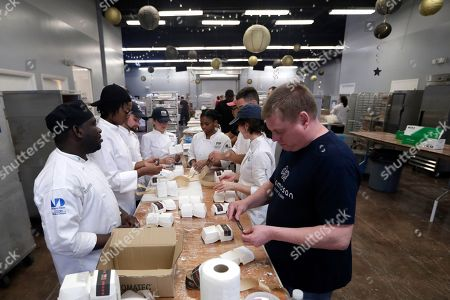 Stock Photo of Students with Florida International University's culinary school prepare packaging for the Morimoto entry in the burger bash competition at the Miami Rescue Mission in Miami. From Rachael Ray to Bobby Flay, the biggest names in the culinary world are in Miami starting Thursday for the South Beach Wine and Food Festival. And they're getting help in their prep kitchen from an unlikely source, a local homeless shelter. The festival partnered with the Miami Rescue Mission and Florida International University's culinary school