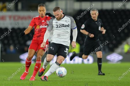 Stock Image of Derby County midfielder/coach Wayne Rooney  shields the ball from Fulham defender Michael Hector during the EFL Sky Bet Championship match between Derby County and Fulham at the Pride Park, Derby