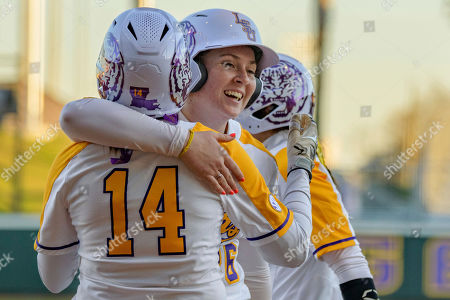 Stock Image of LSU catcher Morgan Cummins, center, celebrates scoring a run with Anna Jones (14), during an NCAA softball game against Belmont, in Baton Rouge, La