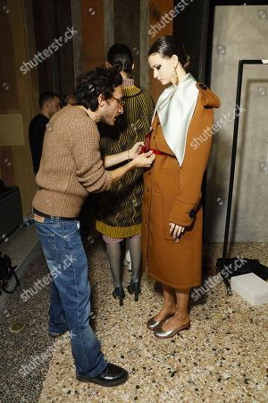 Marco De Vincenzo adjusts a belt on a model