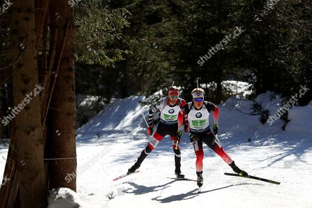 Stock Image of Johannes Dale of Norway skis, followed by Simon Eder of Austria, left, during the men's 4x7.5 km relay competition at the Biathlon World Championships in Antholz, Italy