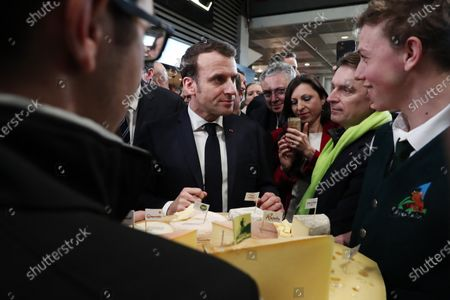French President Emmanuel Macron speaks with a cheese producer during a visit to the 57th International Agriculture Fair (Salon international de l'Agriculture) at the Porte de Versailles exhibition center in Paris, 22 February 2020. The International Agriculture Fair 'Salon International de l'agriculture' (SIA) at the Paris Expo Porte de Versailles runs from 22 February to 01 March 2020.