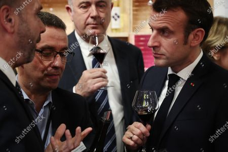 French President Emmanuel Macron holds a glass of red wine during a visit to the 57th International Agriculture Fair (Salon international de l'Agriculture) at the Porte de Versailles exhibition center in Paris, 22 February 2020. The International Agriculture Fair 'Salon International de l'agriculture' (SIA) at the Paris Expo Porte de Versailles runs from 22 February to 01 March 2020.