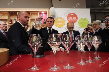 French President Emmanuel Macron holds a bottle of wine during a visit to the 57th International Agriculture Fair (Salon international de l'Agriculture) at the Porte de Versailles exhibition center in Paris, 22 February 2020. The International Agriculture Fair 'Salon International de l'agriculture' (SIA) at the Paris Expo Porte de Versailles runs from 22 February to 01 March 2020.