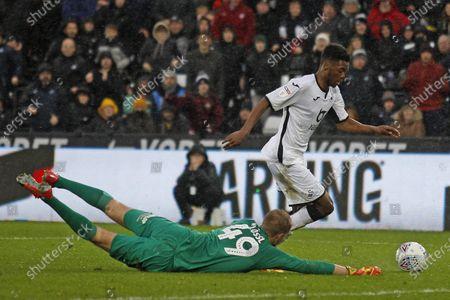 Jordan Garrick of Swansea City rounds Jonas Lossl of Huddersfield Town to score his side's third goal