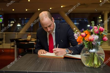 Prince William signs the visitors book.