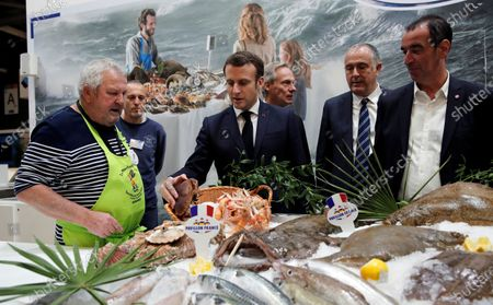 French President Emmanuel Macron(C)  visits the French fishing stand during the 57th International Agriculture Fair (Salon de l'Agriculture) at the Porte de Versailles exhibition center in Paris, France, 22 February 2020. The International Agriculture Fair 'Salon International de l'agriculture' (SIA) at the Paris Expo Porte de Versailles runs from 22 February to 01 March 2020.