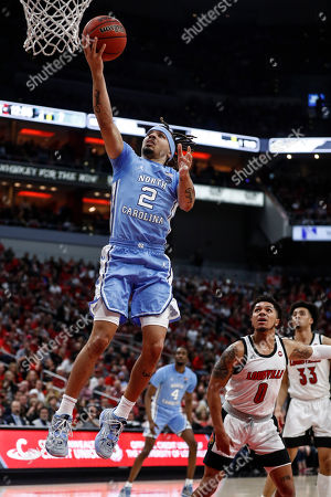 North Carolina guard Cole Anthony (2) shoots a layup in front of Louisville guard Lamarr Kimble (0) during an NCAA college basketball game, in Louisville, Ky