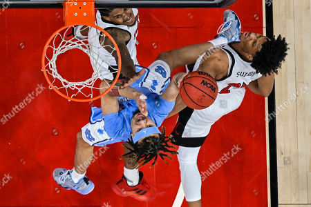 North Carolina guard Cole Anthony (2) shoots over Louisville forward Dwayne Sutton (24) and forward Malik Williams (5) during an NCAA college basketball game, in Louisville, Ky. Louisville won 72-55