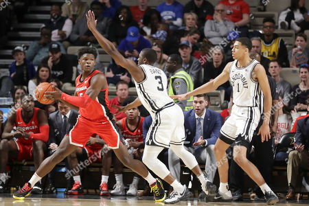 Georgia guard Anthony Edwards, left, is defended by Vanderbilt's Maxwell Evans (3) and Dylan Disu (1) in the second half of an NCAA college basketball game, in Nashville, Tenn