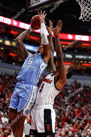 North Carolina forward Armando Bacot (5) shoots as he's defended by Louisville forward Malik Williams (5) during the first half of an NCAA college basketball game, in Louisville, Ky