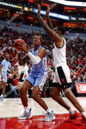North Carolina forward Armando Bacot (5) works for a shot as he's defended by Louisville forward Malik Williams (5) during the first half of an NCAA college basketball game, in Louisville, Ky