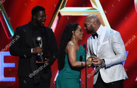 """Winston Duke, Angela Bassett, Dave Bautista. Winston Duke, from left, looks on as Angela Bassett is congratulated by Dave Bautista, right, for her winning the award for outstanding actress in a drama series for """"9-1-1"""" at the 51st NAACP Image Awards at the Pasadena Civic Auditorium, in Pasadena, Calif"""