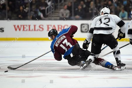 Colorado Avalanche right wing Valeri Nichushkin, left, falls as eh passes the puck while under pressure from Los Angeles Kings center Trevor Moore during the third period of an NHL hockey game, in Los Angeles. The Avalanche won 2-1 in overtime