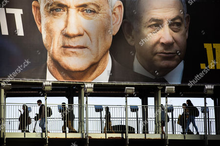 People walk on a bridge under an election campaign billboard for the Blue and White party, the opposition party led by Benny Gantz, left, in Ramat Gan, Israel. Prime Minister Benjamin Netanyahu of the Likud party is pictured at right. Israel finds itself in a familiar place after a tumultuous election campaign, with iconoclastic politician Avigdor Lieberman seemingly in control of the country's fate. Opinion polls ahead of the March 2 vote show that neither Netanyahu nor his challenger Gantz will be able to form a coalition government without him. Lieberman remains cagey about his intentions, raising the possibility his brinkmanship could end up forcing yet another election