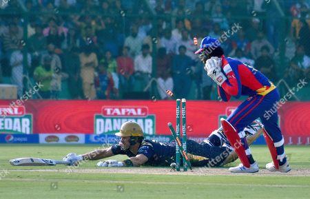 Karachi Kings wicketkeeper Chadwick Walton, right, watches the umpire after run out to Quetta Gladiators batsman Shane Watson during their Pakistan Super League T20 cricket match at National Stadium in Karachi, Pakistan