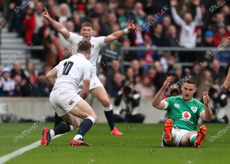 Jonny Sexton (right) of Ireland sits on the pitch dejected after  England's opening Try