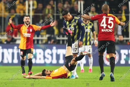 Fenerbahce's Nabil Dirar (up C) and Galatasaray's Omer Bayram (bottom) react during the Turkish Super League soccer derby match between Fenerbahce and Galatasaray in Istanbul, Turkey, 23 February 2020.