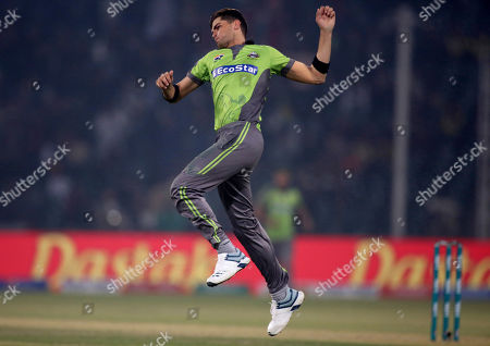 Lahore Qalandars pacer Shaheen Shah Afridi jumps to celebrate after taking the wicket of Islamabad United batsman Asif Ali during their Pakistan Super League T20 cricket match at Gaddafi stadium in Lahore, Pakistan