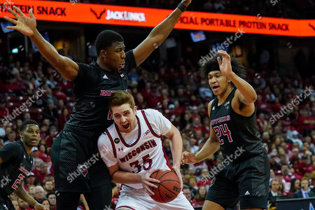 Stock Image of Rutgers' Myles Johnson (15) battles against Rutgers' Shaq Carter, left, and Ron Harper (24) during the second half of an NCAA college basketball game, in Madison, Wis. Wisconsin won 79-71