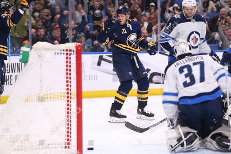 Buffalo Sabres forward Kyle Okposo (21) puts the puck past Winnipeg Jets goalie Connor Hellebuyck (37) during the first period of an NHL hockey game, in Buffalo, N.Y